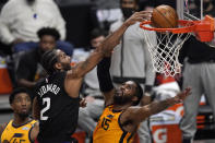 Los Angeles Clippers forward Kawhi Leonard, center, dunks over Utah Jazz center Derrick Favors, right, as guard Donovan Mitchell watches during the first half in Game 4 of a second-round NBA basketball playoff series Monday, June 14, 2021, in Los Angeles. (AP Photo/Mark J. Terrill)
