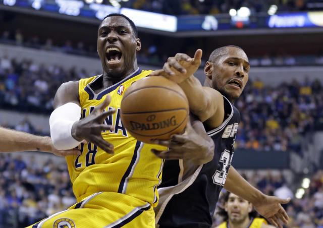 Indiana Pacers center Ian Mahinmi, left, and San Antonio Spurs forward Boris Diaw battle for rebound in the first half of an NBA basketball game in Indianapolis, Monday, March 31, 2014. (AP Photo/Michael Conroy)