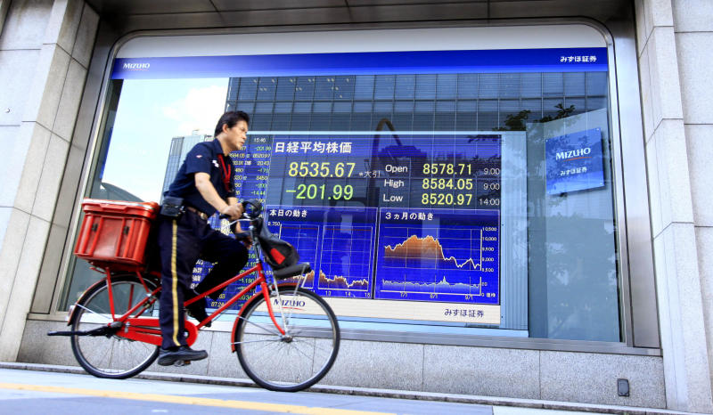 A postal deliverer pedals past an electronic stock board at a securities firm in Tokyo, Japan, Monday, Sept. 12, 2011.  Asian stock markets fell sharply Monday amid fresh anxiety over Europe's debt problems and a potential default by Greece that would wreak havoc on the global economy. Japan's benchmark Nikkei index hit a 28-month low. Japan's Nikkei 225 stock average lost 2.3 percent to 8,535.67,  its lowest closing level since April 2009.  (AP Photo/Shizuo Kambayashi)