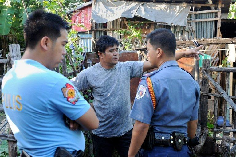 Philippine police talk to a relative of a victim following a deadly gun rampage in Kawit, about 40 kms (25 miles) south of Manila, on January 4, 2013. The gunman armed with a semi-automatic pistol killed at least seven people and wounded 12 others, before being shot and killed by police