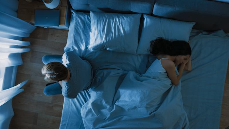 Depressed and Stressed Young Man Sits on the Edge of Bed at Night, Suffering From Insomnia Because of Sex Problems. His Young Wife Lies Beside Him Feeling Empathy.
