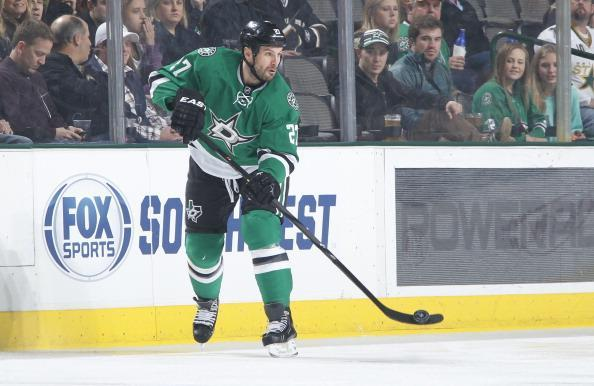 DALLAS, TX - JANUARY 4: Aaron Rome #27 of the Dallas Stars handles the puck against the Detroit Red Wings at the American Airlines Center on January 4, 2014 in Dallas, Texas. (Photo by Glenn James/NHLI via Getty Images)