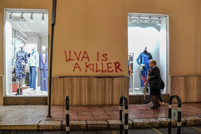 A resident walks past a clothes shop in central Taranto, southern Italy, on November 7, 2019, with a tag refering to the city's steel manufacturing giant Arcelor Mittal Italia (ex ILVA ) plant. - The world steel giant ArcelorMittal announced on November 4, 2019 that it was cancelling the takeover of the Italian company Ilva, after the withdrawal of criminal environmental protection for the managers of the Taranto site, which is currently being cleaned up. (Photo by Andreas SOLARO / AFP) (Photo by ANDREAS SOLARO/AFP via Getty Images)