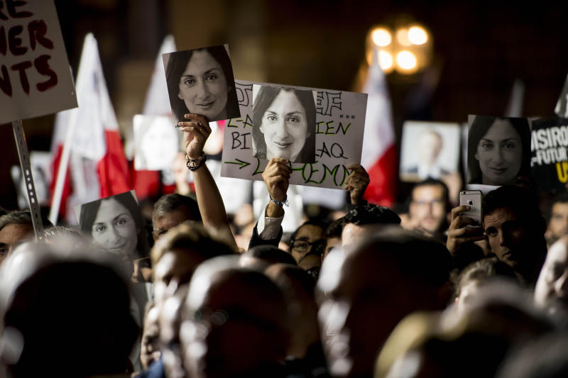 Protesters hold photos during a protest outside the office of the Prime Minster of Malta by civil groups Occupy Justice and Republica Friday, Nov. 29, 2019 in Valletta, calling for the resignation of Malta Prime Minister Joseph Muscat after his chief of staff Keith Scembri was arrested and questioned regarding the murder of slain journalist Daphne Caruana Galizia. Muscat said Friday that police found no grounds to hold Keith Schembri, his former chief of staff in custody.  (AP Photo/Rene Rossignaud)