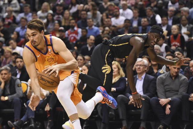 Phoenix Suns forward Dario Saric gets around Toronto Raptors forward Pascal Siakam during the first half of an NBA basketball game Friday, Feb. 21, 2020, in Toronto. (Frank Gunn/The Canadian Press via AP)