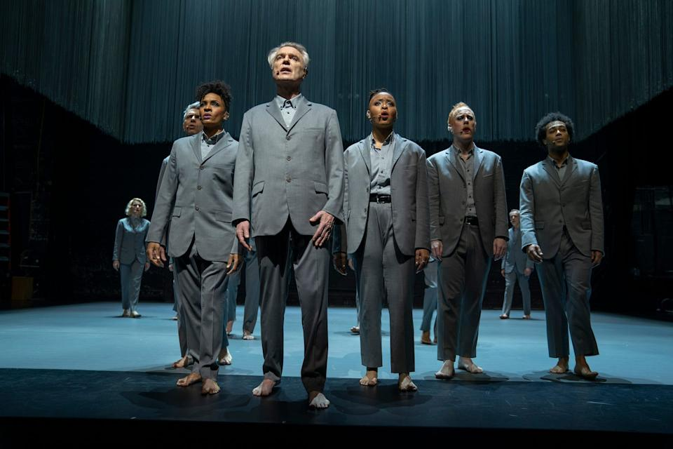 """David Byrne (center) is host, frontman and ringmaster of """"American Utopia,"""" a filmed version of the Broadway show directed by Spike Lee."""