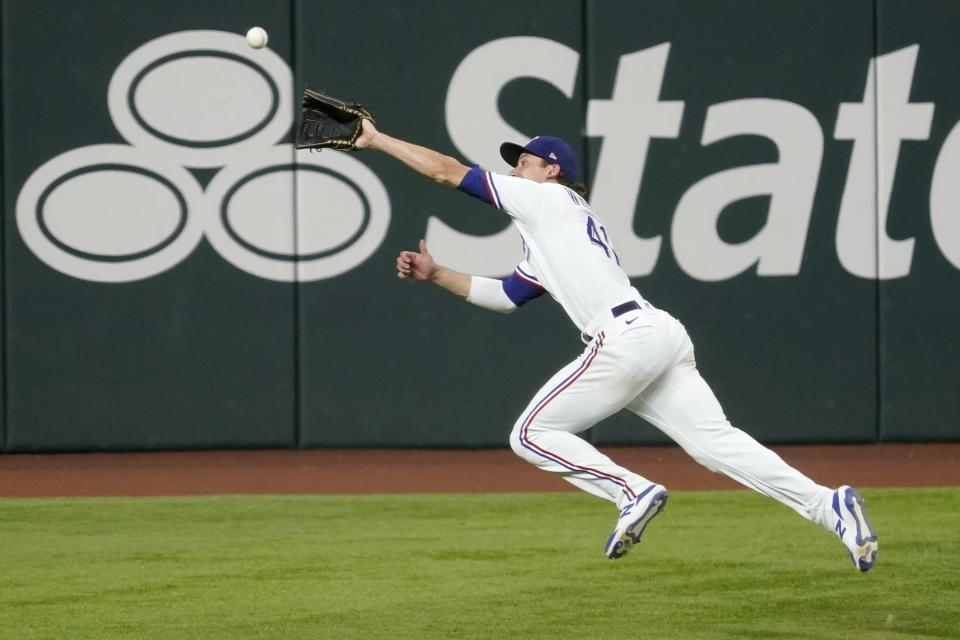 Texas Rangers left fielder Eli White is unable to reach a two-RBI double hit by Los Angeles Angels' Jo Adell in the third inning of a baseball game in Arlington, Texas, Tuesday, Aug. 3, 2021. The hit scored Justin Upton and Phil Gosselin. (AP Photo/Tony Gutierrez)