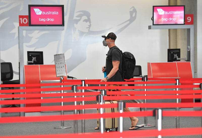 A man walks through an empty Brisbane Domestic Airport wearing a face mask.