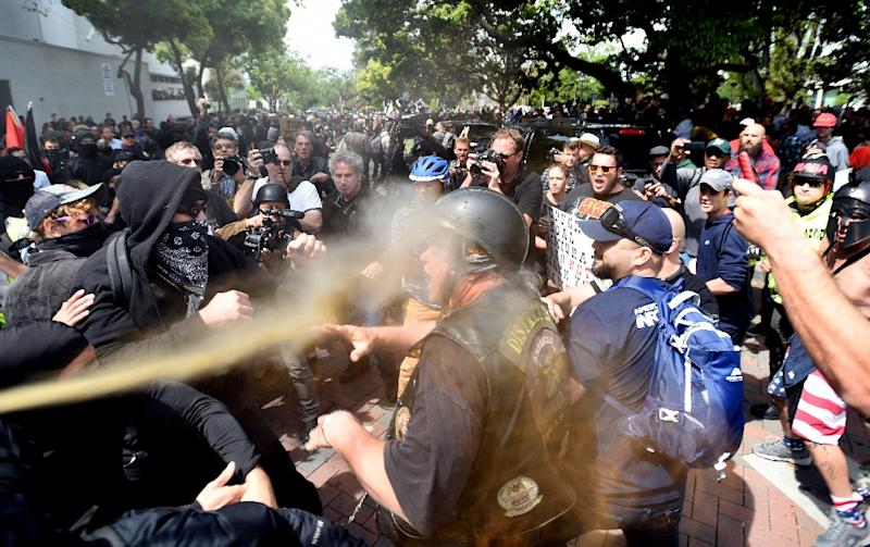 A man gets sprayed with a chemical irritant as multiple fights break out between Trump supporters and anti-Trump protesters in Berkeley, California on April 15, 2017 (AFP Photo/Josh Edelson)