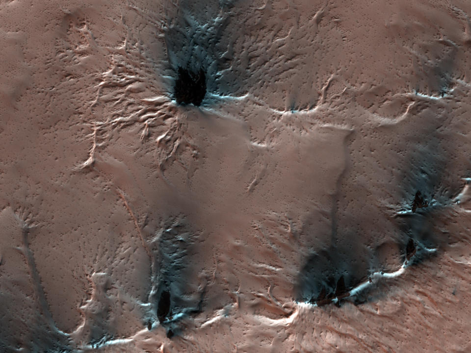 "Strange spider-like features creep on the surface of Mars in this image taken by the High-Resolution Imaging Science Experiment (HiRISE) camera on board NASA's Mars Reconnaissance Orbiter. These spidery landforms are what scientists call ""araneiform"" terrain, which literally translates to ""spider-like."" The features arise because the Red Planet's climate is so cold that during the Martian winter, carbon dioxide freezes from the atmosphere and accumulates as ice on the surface. When that ice begins to thaw in the spring, that carbon dioxide sublimates back into the atmosphere, or turns from a solid to a gas, leaving behind deep troughs in the terrain as gas is trapped below the surface."