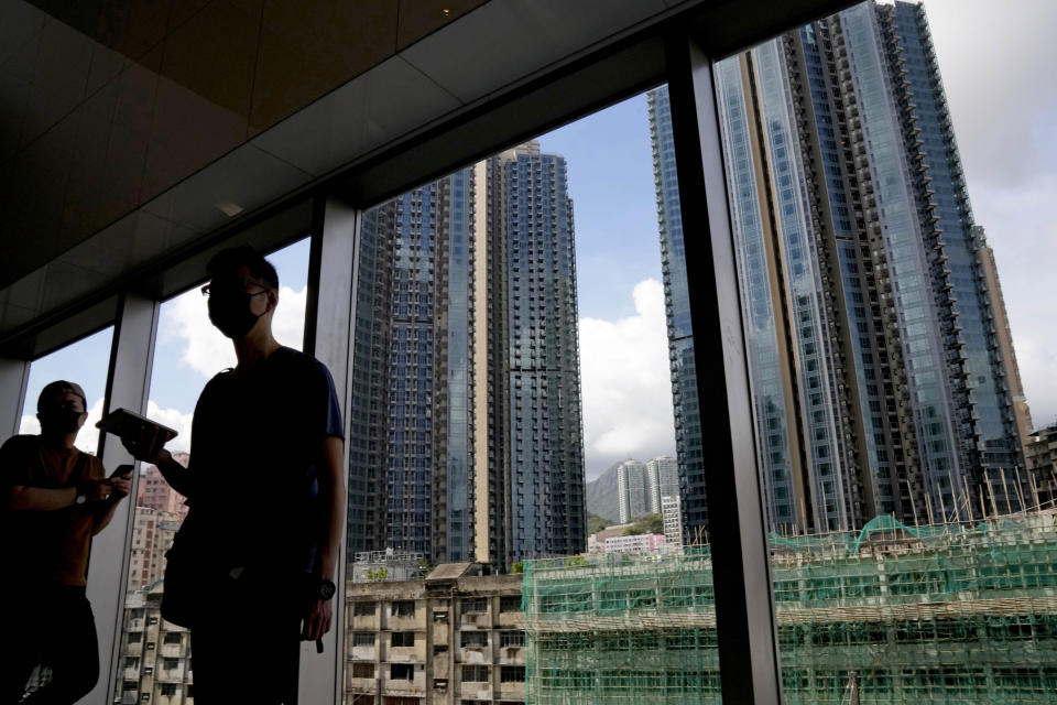 People stand in front of the Grand Central residential building complex where a HK$10.8 million (US$1.4 million) 449 square feet single-room unit will be offered as a prize in a lucky draw, in Hong Kong. Coronavirus vaccine incentives offered by Hong Kong companies, including a lucky draw for an apartment, a Tesla car and even gold bars, are helping boost the city's sluggish inoculation rate. (AP Photo/Kin Cheung)