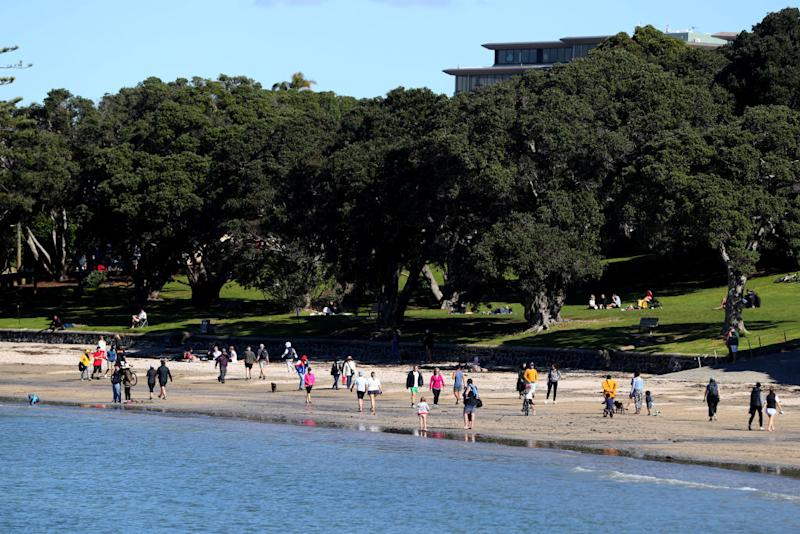 Members of the public walk along Takapuna beach in Auckland. Source: Getty
