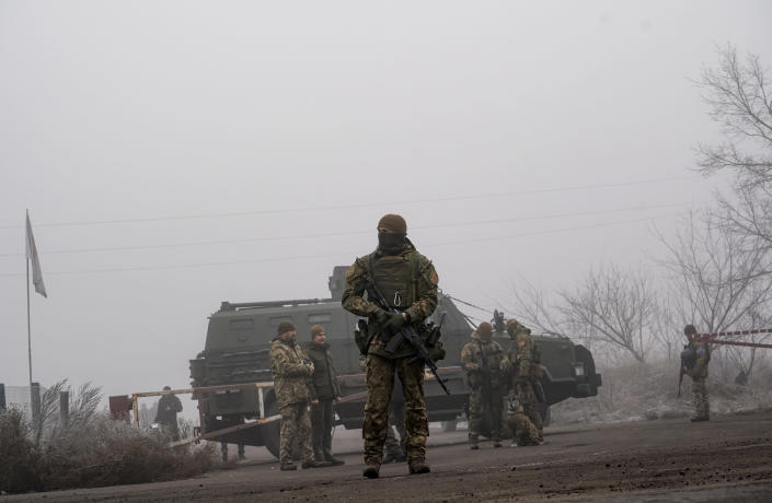 Ukrainian soldiers guard an area during war prisoners exchange near Odradivka, eastern Ukraine, Sunday, Dec. 29, 2019. Ukrainian forces and Russia-backed rebels in eastern Ukraine have begun exchanging prisoners in a move aimed at ending their five-year-long war. The move is part of an agreement brokered earlier this month at a summit of the leaders of Ukraine, Russia, Germany and France. (AP Photo/Evgeniy Maloletka)