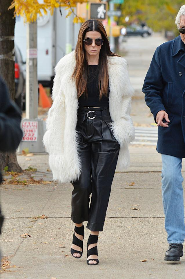 """<p>It's been awhile since we've seen Sandra Bullock in the spotlight – but she's back on the set of """"Oceans 8,"""" which means hopefully we'll be seeing her light up the red carpet soon. In the meantime, her off-duty looks are doing the trick. She was out and about on set in high-waisted leather pants, a crop top, strappy sandals and a furry coat on Nov. 10. <i>(Photo by Josiah Kamau/BuzzFoto via Getty Images)</i><br /></p>"""