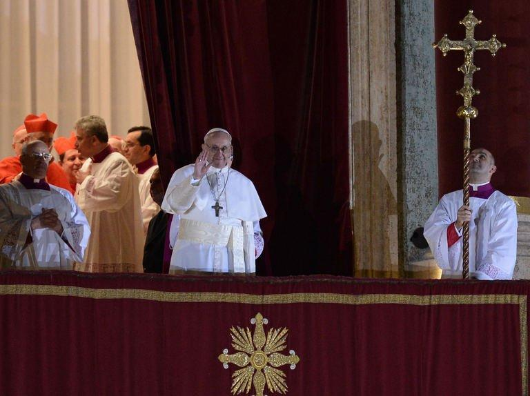 Argentina's Jorge Bergoglio, elected Pope Francis I (C) appears at the window of St Peter's Basilica's balcony after being elected the 266th pope of the Roman Catholic Church on March 13, 2013 at the Vatican