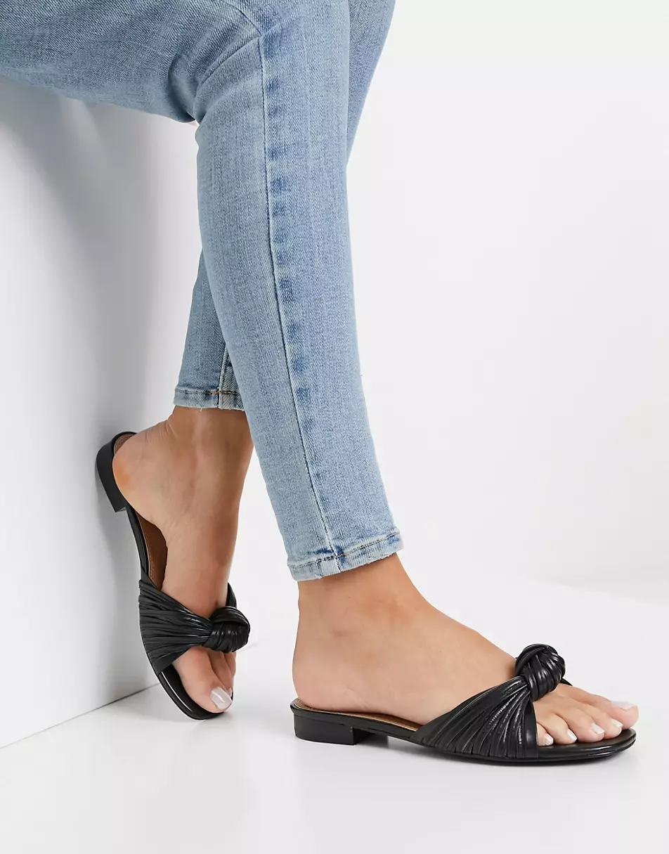 """<h2>Cheap Slide Sandals<br></h2><br>The only thing easier than adding these <a href=""""https://www.refinery29.com/en-us/pool-slides"""" rel=""""nofollow noopener"""" target=""""_blank"""" data-ylk=""""slk:affordable slip-ons"""" class=""""link rapid-noclick-resp"""">affordable slip-ons</a> to your cart is adding them to your summer outfit once they arrive at your doorstep.<br><br><strong>ASOS DESIGN</strong> Freddie Knotted Mule Sandals, $, available at <a href=""""https://go.skimresources.com/?id=30283X879131&url=https%3A%2F%2Fwww.asos.com%2Fus%2Fasos-design%2Fasos-design-freddie-knotted-mule-sandals-in-black%2Fprd%2F21805032"""" rel=""""nofollow noopener"""" target=""""_blank"""" data-ylk=""""slk:ASOS"""" class=""""link rapid-noclick-resp"""">ASOS</a>"""