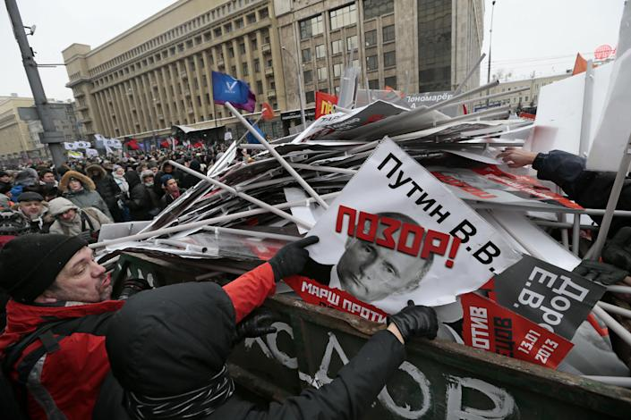 "People throw portraits brought to the rally in the garbage during a protest rally in Moscow, Russia, Sunday, Jan. 13, 2013, with the portrait of Russian President Vladimir Putin in the center. Thousands of people are gathering in central Moscow for a protest against Russia's new law banning Americans from adopting Russian children. They carry posters of President Vladimir Putin and members of Russia's parliament who overwhelmingly voted for the law last month. The posters have the word ""Shame"" written in red over the faces and proclaim that Sunday's demonstration is a ""March Against the Scum"" who enacted the law. (AP Photo/Ivan Sekretarev)"