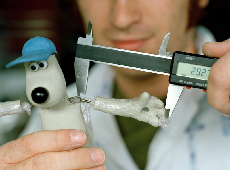 Jay Smart, Junior Model Maker, measuring Gromit. The average size of Wallace and Gromit is 8 inches although some are 6 or even 4 inches depending on the size of the film set. (Photo by In Pictures Ltd./Corbis via Getty Images)