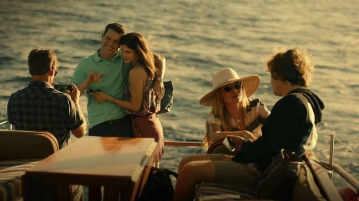 On the back of a boat at sea, Mark takes a photo of Shane and Rachel while Nicole and Quinn talk together in the foreground