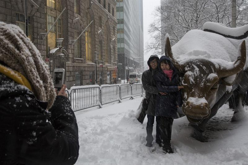 Tourists pose for photo with the Charging Bull during a morning snow in New York's financial district near Wall Street
