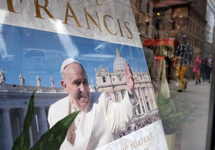 People are reflected on a shop window displaying a portrait of Pope Francis in New York on September 22, 2015 (AFP Photo/Jewel Samad)