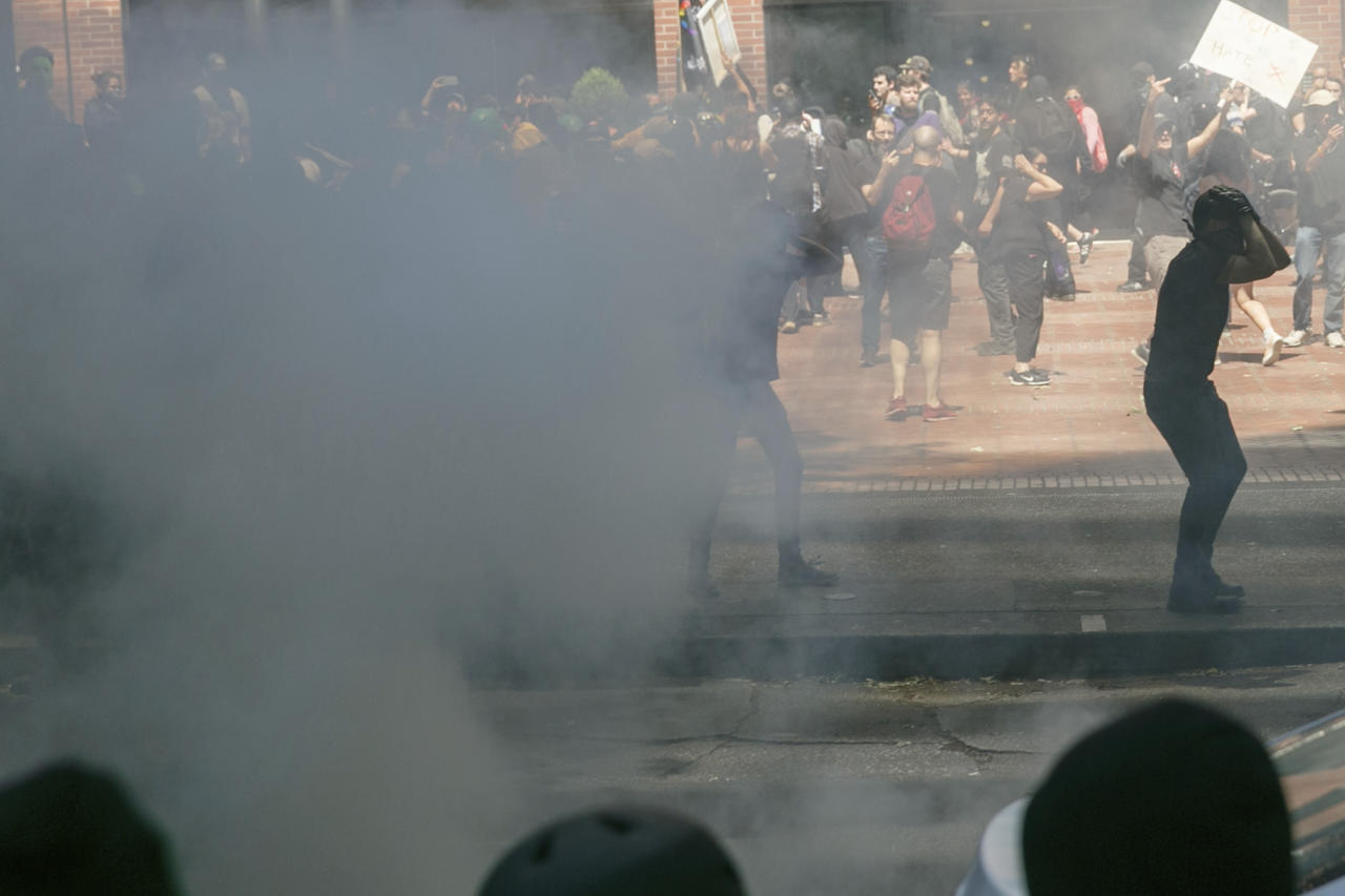 <p>Police push protesters back with tear gas and flash-bang grenades during a rally in Portland, Ore., Saturday, Aug. 4, 2018. (Photo: John Rudoff/AP) </p>