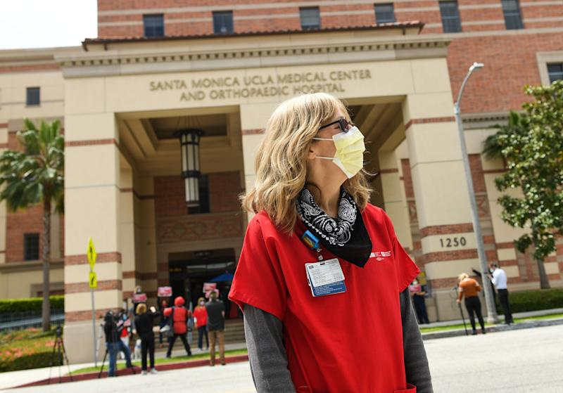 A nurse wearing a protective mask participates in a rally to support the National Nurses United and California Nurses Association's demand for personal protective equipment for healthcare workers across the state at UCLA Medical Center Santa Monica, in April 13, 2020, in Santa Monica, California. (Photo by VALERIE MACON / AFP) (Photo by VALERIE MACON/AFP via Getty Images)