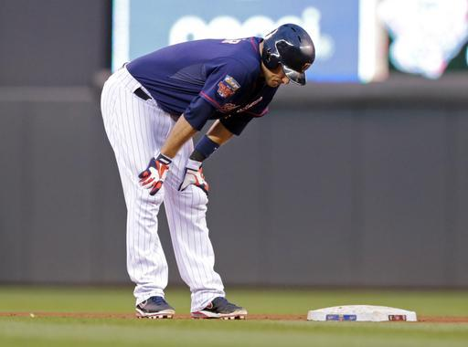 Minnesota Twins' Joe Mauer holds his legs after he pulled up to second with a two-run double off Kansas City Royals pitcher James Shields in the fourth inning of a baseball game, Tuesday, July 1, 2014, in Minneapolis. Mauer later left the game. (AP Photo/Jim Mone)