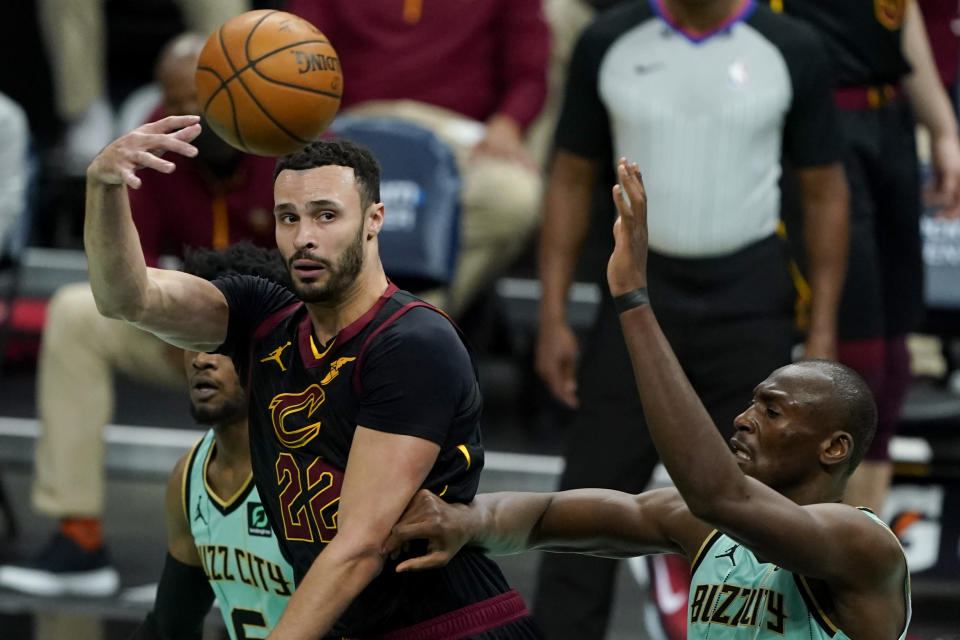 Cleveland Cavaliers forward Larry Nance Jr. passes over Charlotte Hornets center Bismack Biyombo during the first half of an NBA basketball game on Friday, April 23, 2021, in Charlotte, N.C. (AP Photo/Chris Carlson)