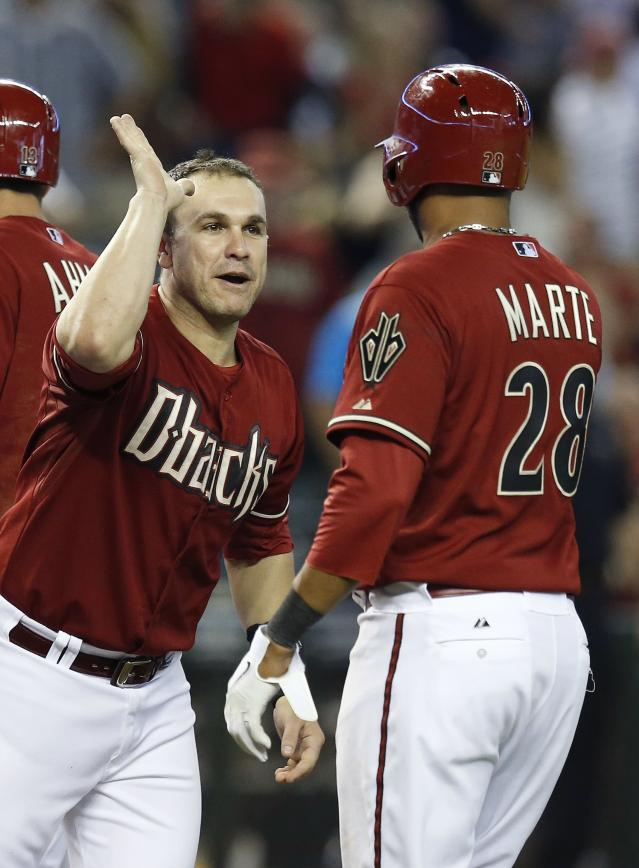Arizona Diamondbacks' Miguel Montero, left, congratulates Andy Marte (28) on his game-winning RBI on a fielder's choice during the 10th inning of a baseball game against the Pittsburgh Pirates on Sunday, Aug. 3, 2014, in Phoenix. The Diamondbacks defeated the Pirates 3-2. (AP Photo/Ross D. Franklin)