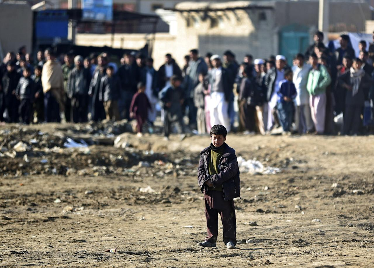 An Afghan child looks towards the site of a suicide bombing that struck near a NATO convoy in the Afghan capital Kabul, Afghanistan, Monday, Feb. 10, 2014. Taliban-affiliated militants have stepped up attacks in the final year of the international coalition's 13-year combat mission in Afghanistan, seeking to shake confidence in the Kabul government's ability to keep order after they assumed full security responsibility last year. (AP Photo/Massoud Hossaini)