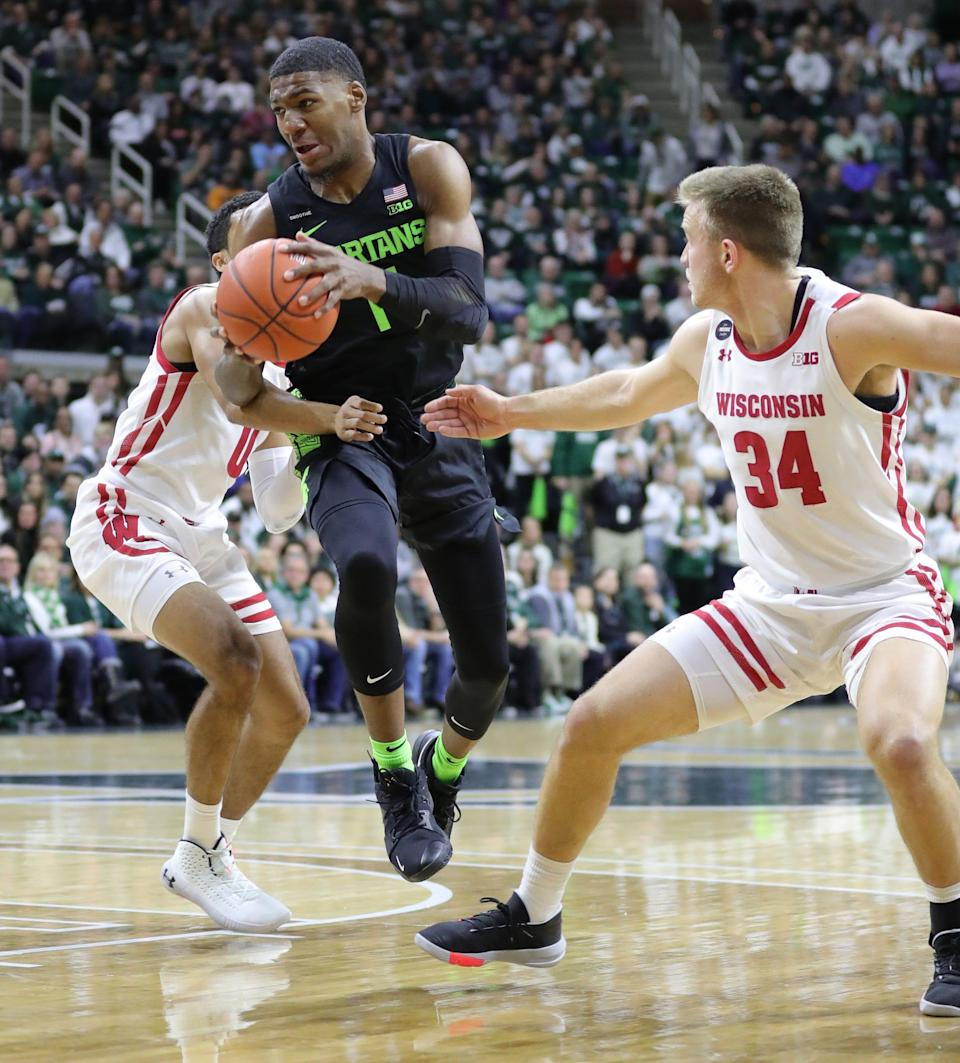 Michigan State Spartans forward Aaron Henry drives against Wisconsin Badgers guards D'Mitrik Trice, left, and Brad Davison, right, during the first half at the Breslin Center in East Lansing, Friday, Jan. 17, 2020.