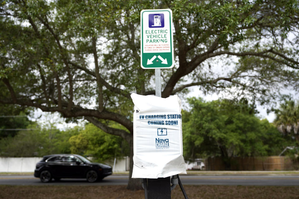 A parking area with charging stations for electric vehicles at a public park is seen Thursday, April 1, 2021, in Orlando, Fla. As part of an infrastructure proposal by the Biden administration, $174 billion will be set aside to build 500,000 electric vehicle charging stations, electrify 20% of school buses and electrify the federal fleet, including U.S. Postal Service vehicles.(AP Photo/John Raoux)