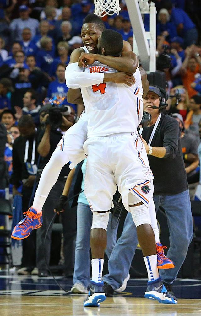 Florida forward Will Yeguete, left, and center Patric Young (4) celebrate after beating Kentucky in an NCAA college basketball game in the championship for the Southeastern Conference tournament, Sunday, March 16, 2014, in Atlanta. Florida won 61-60. (AP Photo/Atlanta Journal-Constitution, Curtis Compton)