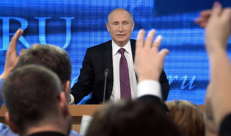 Journalists raise their hands to ask questions of Russia President Vladimir Putin