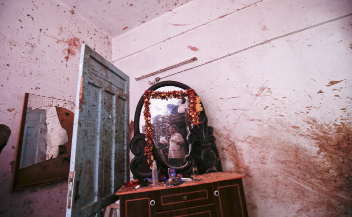 <p>A relative of 23-year-old Palestinian Enas Khammash, who was killed with her toddler in an Israeli airstrike, inspects their bedroom in Deir Al-Balah in the central Gaza Strip on Aug. 9, 2018. Israel struck a series of sites in retaliation for dozens of rockets fired early on August 9. (Photo by Said KhatibAFP/Getty Images) </p>