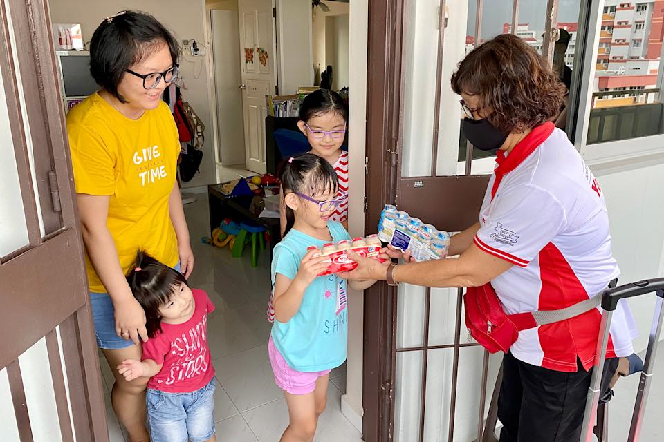 Yakult Lady Chong Wai Yoong, 62, delivers to homemaker Cynthia Widiastuti, 39, and her three young children. (PHOTO: Dhany Osman/Yahoo News Singapore)