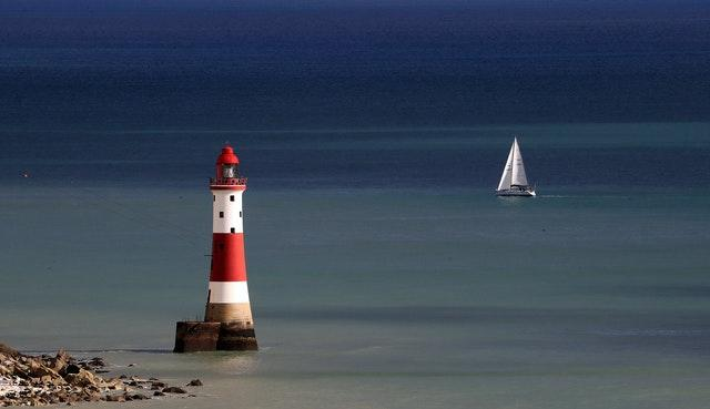 A yacht sails past Beachy Head lighthouse near Eastbourne in Sussex