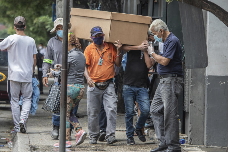 Cemetery workers carry the remains of a person in a cardboard coffin for burial at the General Cemetery in Guayaquil, Ecuador, Monday, April 6, 2020. Guayaquil, a normally bustling city that has become a hot spot in Latin America as the coronavirus pandemic spreads, has untold numbers dying of unrelated diseases that can't be treated because hospitals are overwhelmed. (AP Photo/Luis Perez)