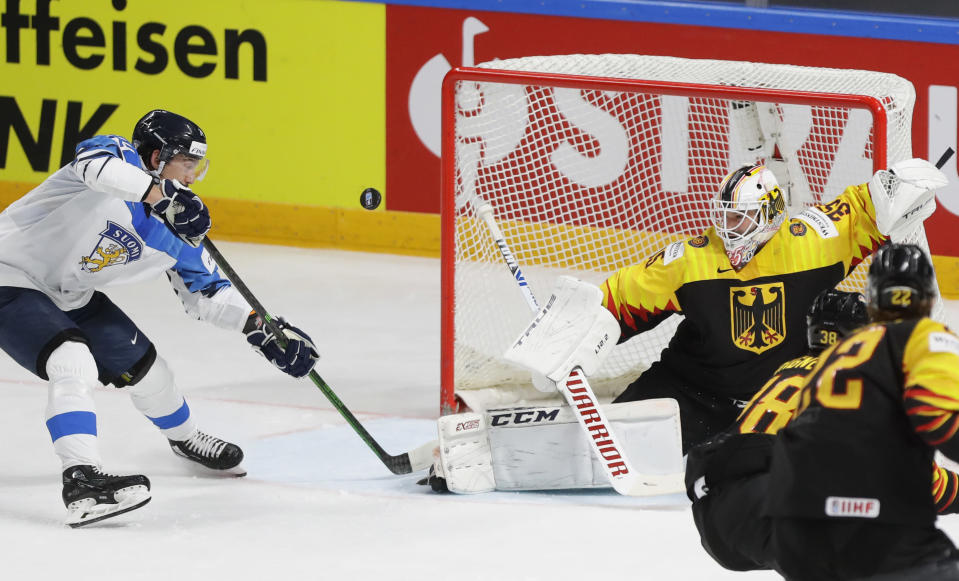 Finland's Hannes Bjorninen, left, tries to score against Germany's goaltender Mathias Niederberger during the Ice Hockey World Championship group B match between Germany and Finland at the Arena in Riga, Latvia, Saturday, May 29, 2021. (AP Photo/Sergei Grits)