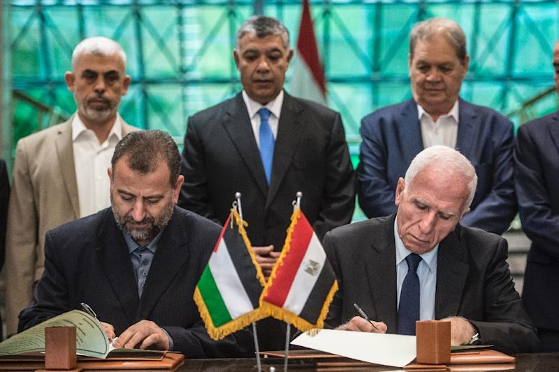 Saleh al-Aruri (L) of Hamas and Fatah's Azam al-Ahmad (R) sign a reconciliation deal at the Egyptian intelligence services headquarters in Cairo on October 12, 2017 (AFP Photo/KHALED DESOUKI)
