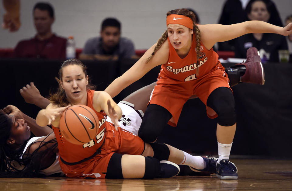 FILE — In this Dec. 21, 2017, file photo, Syracuse forward Digna Strautmane, center, and guard Tiana Mangakahia, right, chase the ball next to a Mississippi State player during the first half of an NCAA college basketball game, in Las Vegas. In spite of everything that's been thrown her way, the smile of Syracuse point guard Tiana Mangakahia and her effervescent persona remain as infectious as ever in the waning weeks of her final season in college. It's in her DNA. (AP Photo/David Becker, File)