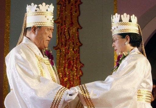 File photo taken in 2002 shows Unification Church founder Sun Myung Moon (L) and his wife Hak Ja Han during a mass wedding ceremony in Seoul. Moon's death robs his Unification Church of the glue that sustained its global following as a cohesive religious and financial force even as membership dwindled from its 1980s peak, analysts say