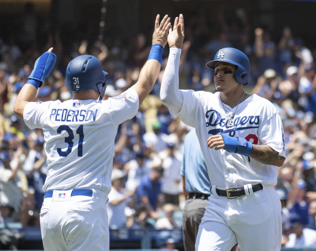 Los Angeles Dodgers' Joc Pederson, left, and Manny Machado celebrate after they score on a two-run double by Brian Dozier during the first inning of a baseball game against the Houston Astros in Los Angeles, Sunday, Aug. 5, 2018. (AP Photo/Kyusung Gong)