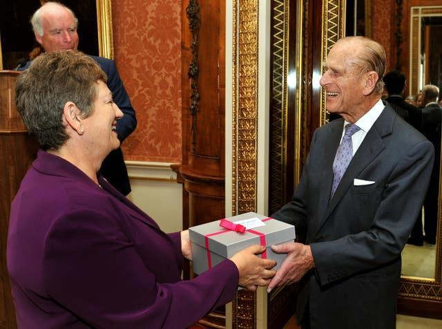 The Duke of Edinburgh receives a pair of ear defenders given to him as a birthday present from Jackie Ballard, chief executive of Action on Hearing Loss charity during a reception for the charity at Buckingham Palace in central London