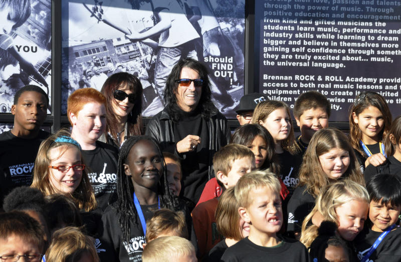 Heavy metal icon Alice Cooper, rear center right, and his wife, Sheryl, rear center left, pose with members of the Boys & Girls Clubs of the Sioux Empire, Wednesday, Oct. 10, 2012, in Sioux Falls, S.D. Cooper was in South Dakota to help his friend, Dollar Loan Center majority owner Chuck Brennan, open a 6,000-square-foot rock ëní roll academy that will be open exclusively to club members. (AP Photo/Dirk Lammers)
