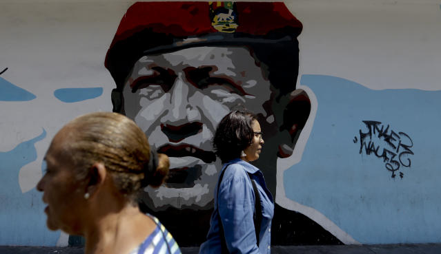 """Pedestrians walk past a mural featuring Venezuela's late President Hugo Chavez, in Caracas, Venezuela, Tuesday, March 19, 2019. Chavez, a former military officer, declared a socialist """"revolution"""" after coming to power in 1999. He was succeeded after his 2013 death by his protege, Nicolas Maduro. (AP Photo/Natacha Pisarenko)"""
