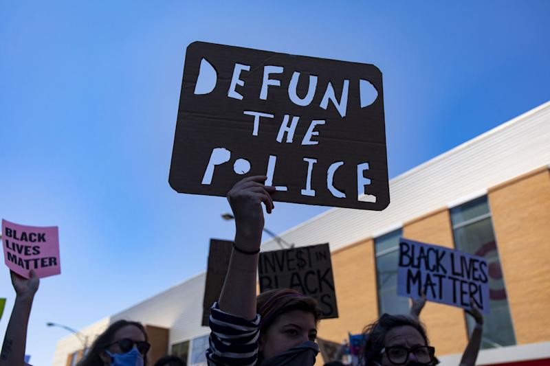 """Protesters carry a """"Defund the Police"""" sign on West Division Street during the March of Justice from Union Park to Cabrini-Green on Saturday, June 6, 2020 in Chicago to demand police accountability. (Brian Cassella/Chicago Tribune/TNS via Getty Images)"""