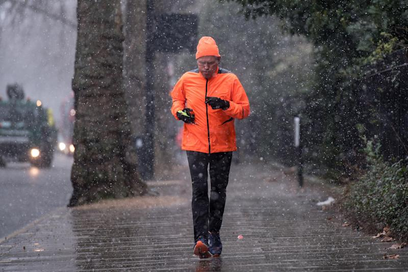 A man runs as snow falls in Kensington Gardens, Hyde Park, during the wintry conditions on Saturday (Getty Images)