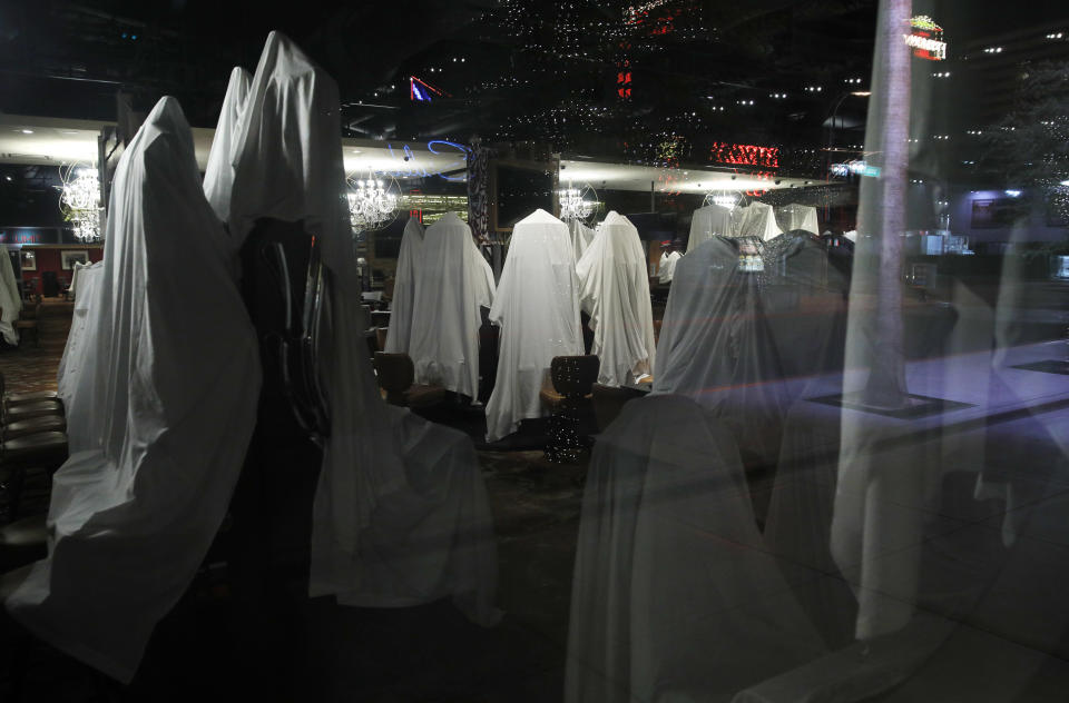 In this April 19, 2020, photo, sheets cover electronic slot machines at a casino shuttered due to the coronavirus in Las Vegas. The glitzy casinos and nightlife attractions of Las Vegas have been quiet since mid-March leaving much of the famous gambling mecca empty during closures due to the coronavirus. (AP Photo/John Locher)